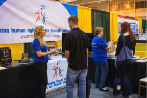 Erica Rodgers, National Director for Youth for Human Rights International (at left) showing the educational booklet to an educator at a teachers' convention