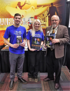 Youth for Human Rights representatives with the Mr. Terry Cherry, Past-President of the National Council for the Social Studies at the annual NCSS Convention showing the different human rights educational materials