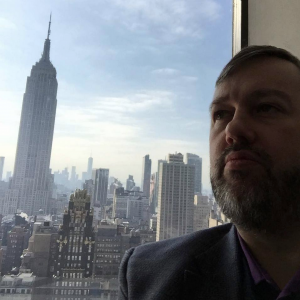 Karl Smith Director of Decision Point in Grace Building in NYC with Empire State building out the window