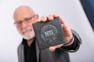 COO of NTI, Alan Hubbard holding up NTI logo on a piece of slate