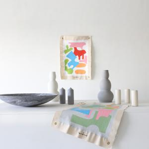 "This is an image of work by The Holey Kids small canvases sized 30"" x 20"" with colorful shapes, sitting by ceramic containers in greys and whites"