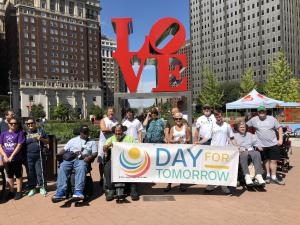 People with and without disabilities holding Day for Tomorrow banner at Love Park in Philadelphia