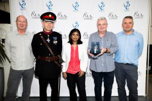 Nigel Biggs receives Queen's Award in the presence of Richard Kornicki and Rupa Huq MP